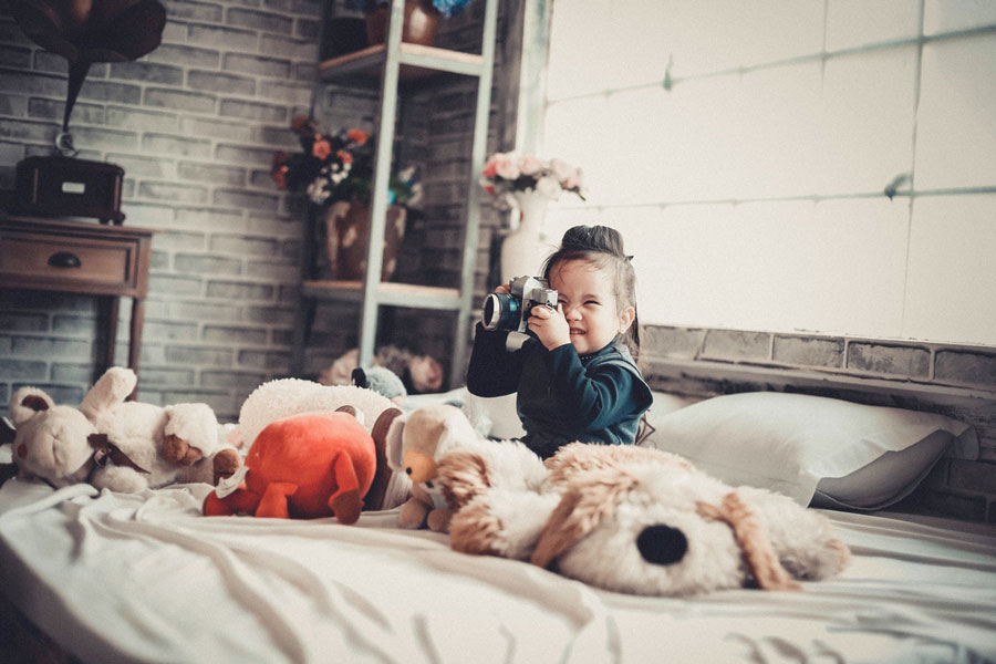 Little girl playing with camera on her bed